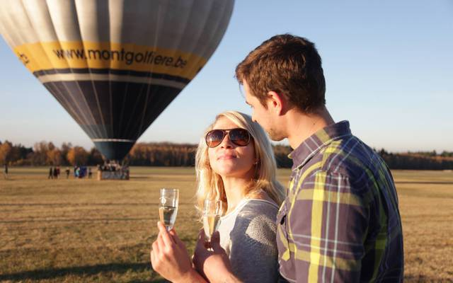 Deux personnes un verre à la main devant une montgolfière