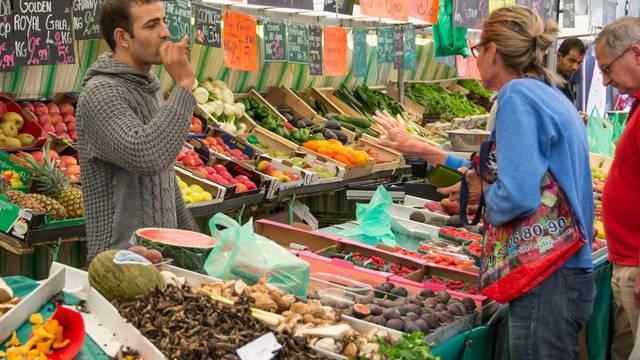 Une personne achetant des légumes dans un marché
