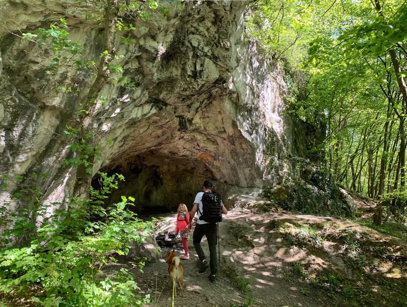 Un papa, sa fille et sin chien avançant vers une grotte