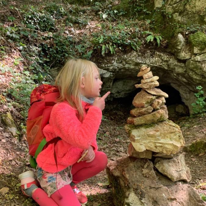 Jeune fille devant une structure en pierre