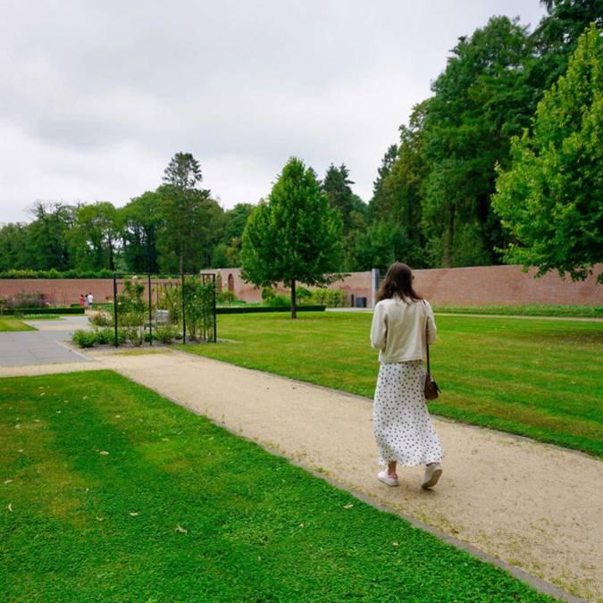 Une dame se promenant dans la parc du château de Jehay